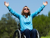 Woman in wheelchair with arms raised outdoors